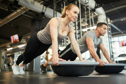 Full length portrait of sportive couple doing balance exercises during workout in modern gym, copy space
