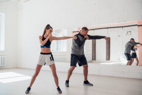 Cute girl learns kickboxing techniques in the gym with an experienced trainer.