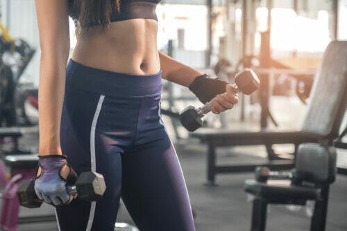 Fitness Frau hebt Handelsgewichte, wobei der Fokus auf Ihr Bauch liegt