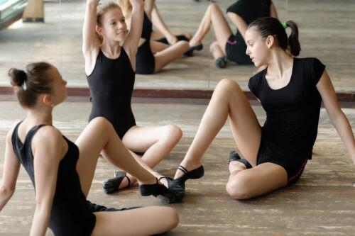 Drei Ballett Tänzerinnen auf dem Boden, während sich Ihre Schuhe berühren