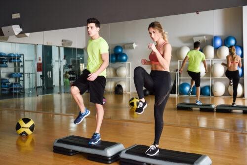 Zwei Menschen trainieren mit Steppers in Gym.