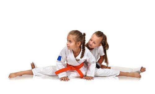 two karate girl sitting on the splits