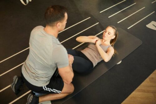 High angle view at muscular coach training young woman doing scrunches in gym, copy space